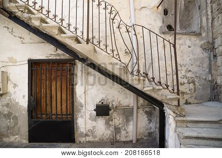 Traditional stair entrance with broken handle and door of Lebanese house in Tyre, Lebanon