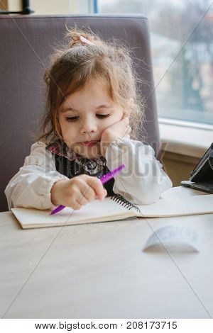 Little kid girl writing or drawing with pen in scetch book.