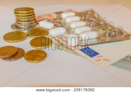 White Tabletts With Euros Banknotes And Coins. Concept Pharmaceutical Business, Cost Of Health, Mede