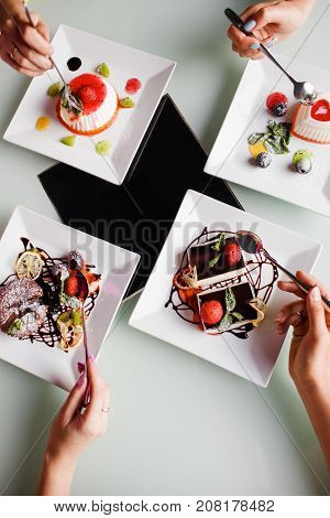 Dinner party top view. Modern bar style. Tasty sweet dessert assortment, unrecognizable people company. Morning breakfast in cafe with friends, antidepressant food concept