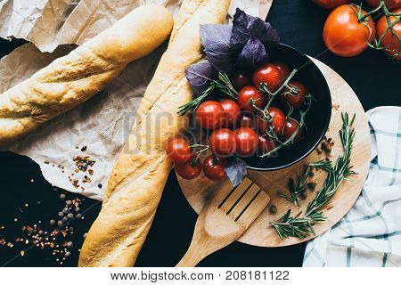 Tasty fresh tomatoes with delicious bread lying on wooden cutting board ready for cooking and making amazing meal for lunch or dinner