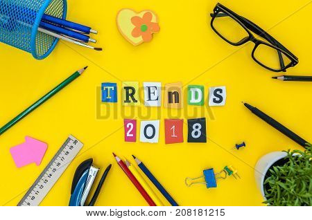 2018 trends - text of carved letters at yellow table background with office or pupil supplies. New year plan.