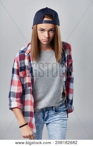 Angry teen girl wearing checkered shirt and baseball cap over grey background looking at camera sullen, walking towards camera