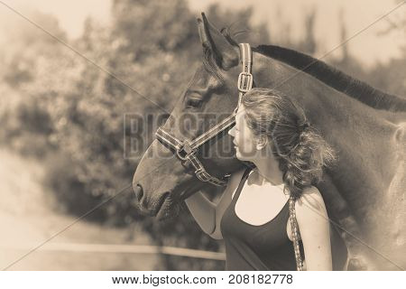 Taking care of animals love and friendship concept. Jockey young girl petting and hugging dark horse on sunny day. Black and white photo