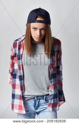 Angry teen girl wearing checkered shirt and baseball cap over grey background looking at camera sullen, front view