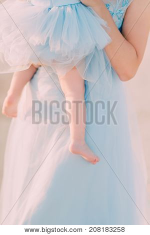 a girl in a blue dress is holding a child