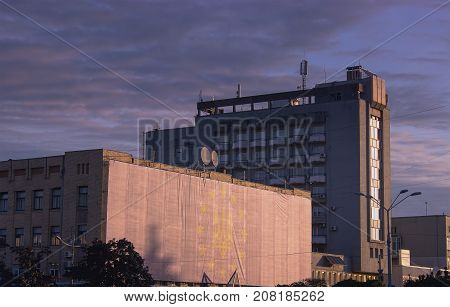 Multistory City Panel Apartment House Against The Evening Sky. Sunlight Reflection