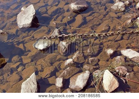 Rusted large chain resting in the water