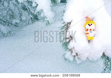 Snowman on snowy fir branch in forest. Christmas fabulous composition