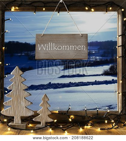 Sign With German Text Willkommen Means Welcome. Window Frame With Winter Landscape With Snow. View To Snowy Scenery Outside. Christmas Tree And Fairy Lights.