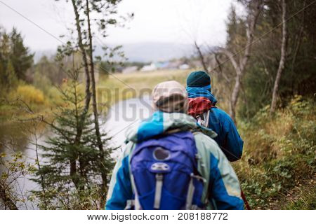 Tourists walking along the river Bank in autumn day