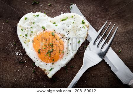 Fried Egg With Heart Shape And Cutlery On Wooden Background