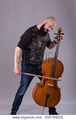 Cellist playing classical music on cello. bearded man fooling around with a musical instrument over gray background