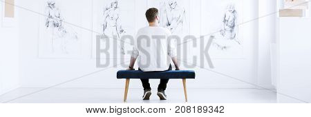 Young man sitting back on the bench alone looking at collection of charcoal drawings hanging on white wall in bright art center