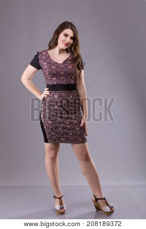 Portrait of a plus size female model posing in broun costume over grey background. Beautiful woman with curvy figure.
