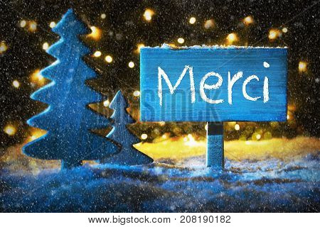 Sign With French Text Merci Means Thank You. Blue Christmas Tree With Snow And Magic Glowing Lights In Backround And Snowflakes. Card For Seasons Greetings.