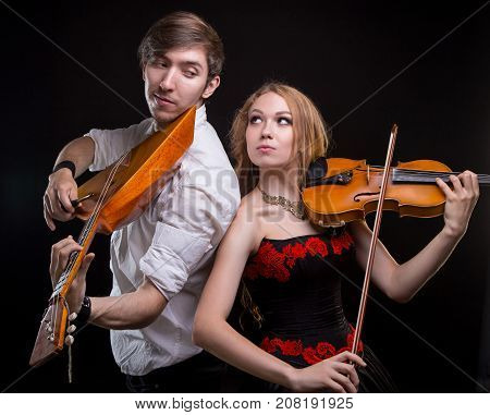 Musical couple with fiddle and balalaika on black background