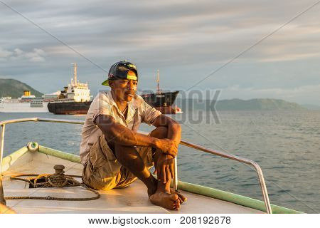 Hell-Ville, Madagascar - December 19, 2015: Malagasy boatman sailing in the rays of the setting sun on the boat in Andavakotakona Bay near Hell-Ville Nosy Be Island Madagascar.