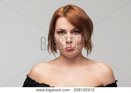 Unpleasant behavior. Female taking offence. Upset young girl portrait on grey background with free space. Capricious attitude, sadness, complaints concept