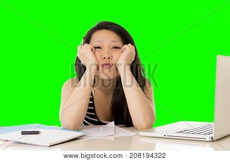 young pretty chinese asian student woman bored tired over worked on her laptop wearing a black shirt isolated on green screen cromakey - chormakey or chroma croma key for composite