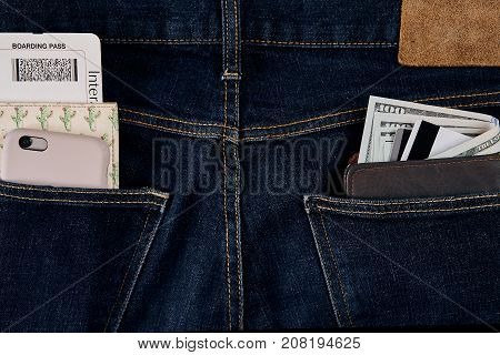 Money, Smart, Debit card and Credit card are in pocket of blue jean. One hundred dollar bills and cards in back of jean pocket in concept of business and finance.