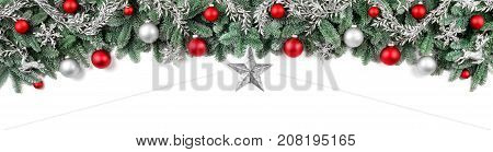 Wide arch-shaped Christmas border isolated on white composed of fresh fir branches and ornaments in red and silver