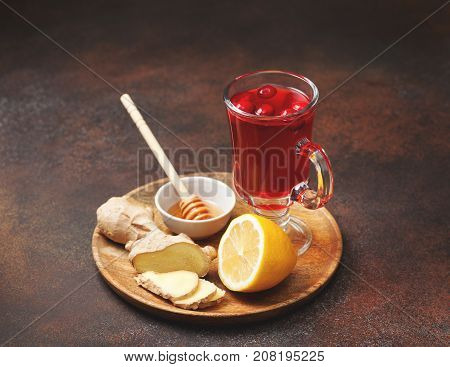 cranberry lemon ginger drink in a glass cup honey half a lemon slices of ginger on an old background