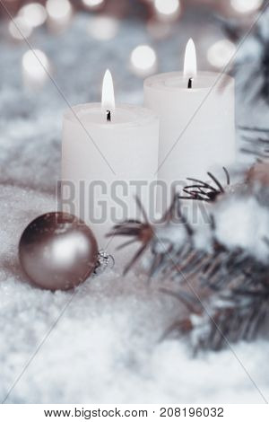 Two burning candles in the snow with bokeh at advent season