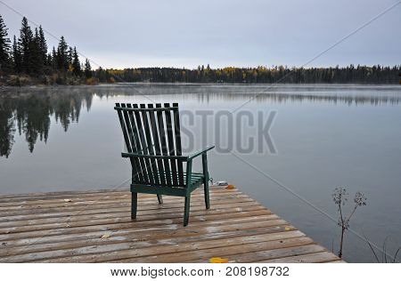 Empty wooden chair on dock on early autumn morning looking out over lake