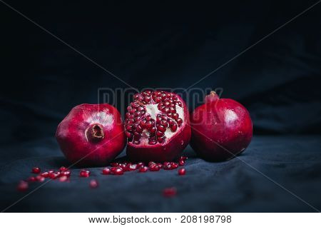 fresh juicy pomegranate diet fruit is a natural antioxidant on black background