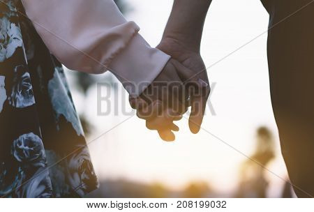 Couple holding for hands on the beach on background ocean sunrise flare silhouette two romantic people looking on rear view evening seascape hipster enjoy sunset together travel holidays vacation