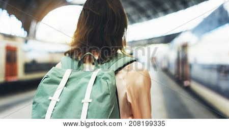 Enjoying travel. Young woman waiting on the station platform with backpack on background electric train. Tourist plan route of railway railroad transport concept trip hipster and lifestyle schedule timetable