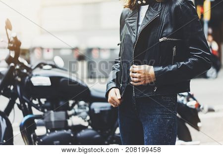 Girl unfastens black leather jacket on background motorcycle in sun flare atmospheric city hipster biker female hands closeup motorbike street lifestyle traveler planing bike route in summer holiday concept