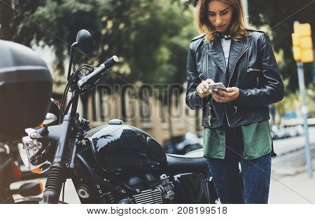 Girl in leather jacket holding smart phone on background motorcycle in sun flare atmospheric city hipster using in female hands and texting mobile motorbike street lifestyle tourist planing route in summer