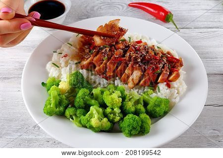 Hand Holds Chopsticks With Piece Of Meat