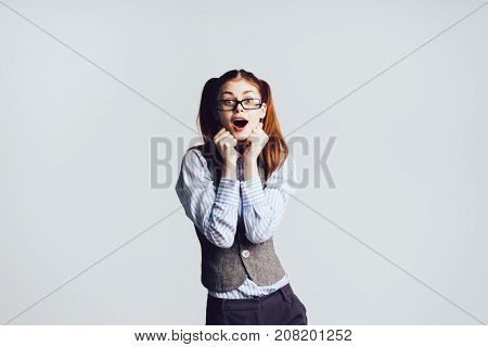 pretty red-haired girl with glasses looks surprised