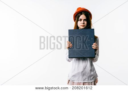 girl in a red hat is holding a folder