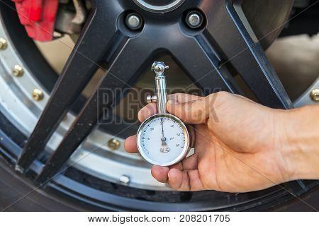 asian man checking air pressure and filling air in the tires of his car