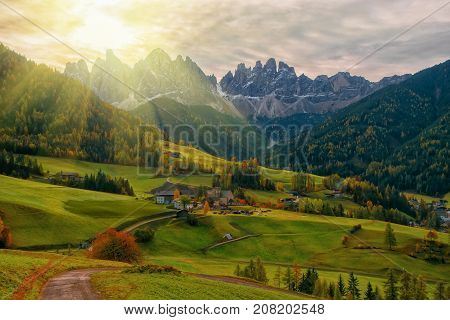 Colorful autumn scenery in Santa Maddalena village with church roads and meadows on foreground and mountain peaks on background at sunrise. Dolomite Alps South Tyrol Italy.