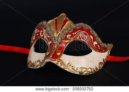 Venetian red and gold carnival mask on black background