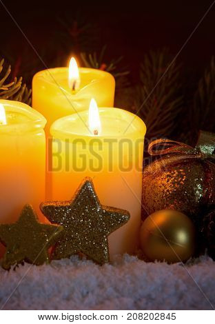 Christmas background with two advent candles and golden decoration.