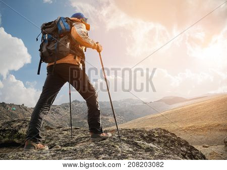 A lonely tourist with a backpack and wearing sunglasses enjoys the views high in the mountains of the Caucasus where there is no grass, the village and snow at sunset. View from the back