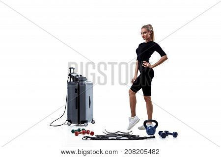 Young woman in Electrical Muscular Stimulation suit standing near EMS station isolated on white background