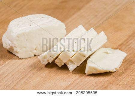 Fresh sliced halloumi cheese from Cyprus on a wooden board surface