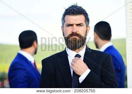 Business Success And Confidence Concept. Businessman With Beard Adjusts Tie