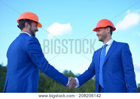 Coworking and construction concept. Board of architects with happy faces in formal wear and helmets shake hands on blue sky background. Builders make deal. Foreman have successful meeting