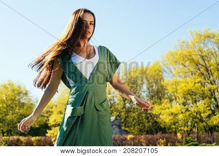 girl in a green dress walking in the autumn park