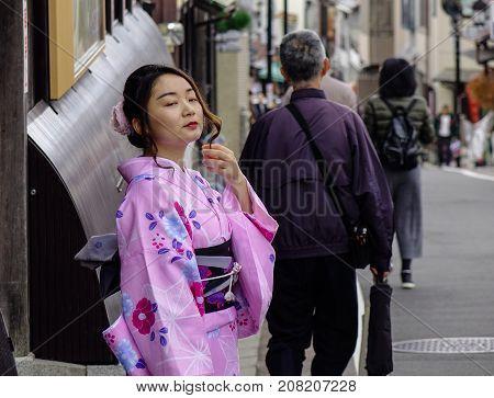 A Woman In Kimono Standing On Street