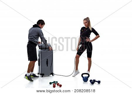 Trainer helps woman to set ems station isolated on white background