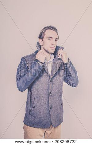 Stylish young man showing a winter coat on a white studio background. Style. Beauty. Fashion. Season